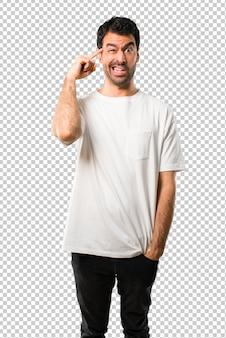頭の上に指を置く狂気のジェスチャーを作る白いシャツと若い男