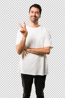 Молодой человек с белой рубашкой счастливым и считая двух с пальцами
