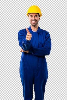 Молодой работник с шлемом, давая пальцы вверх жест и улыбается, потому что случилось что-то хорошее