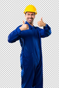 Молодой работник с шлемом, давая пальцы вверх жест и улыбается, потому что был успешным