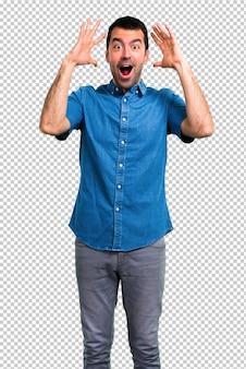 驚きとショックを受けた表情で青いシャツを持つハンサムな男