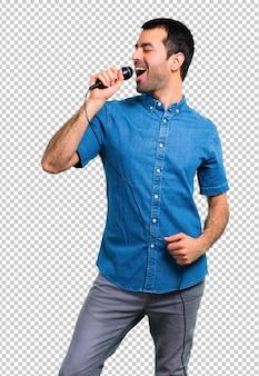 Красивый мужчина в синей рубашке поет с микрофоном