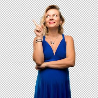 人差し指で素晴らしいアイデアを指している青いドレスと妊娠中のブロンドの女性