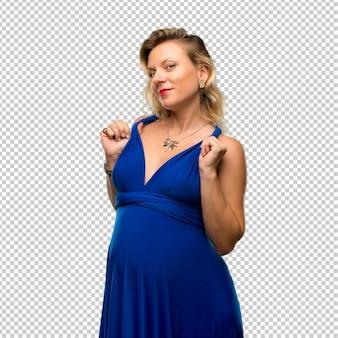 自信を持って自己満足している青いドレスと妊娠中のブロンドの女性