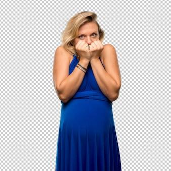 青いドレスで妊娠中のブロンドの女性は少し緊張して怖いです