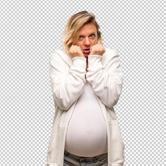 白いトレーナーと妊娠中のブロンドの女性は少し緊張して怖いです