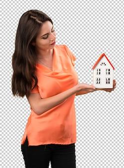 Красивая молодая девушка держит маленький дом