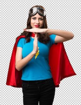 タイムアウトのジェスチャーを作るかなりスーパーヒーローの女の子