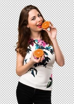 オレンジを保持している美しい若い女の子