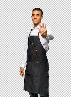 Молодой афро-американский парикмахер человек счастлив и считать три с пальцами