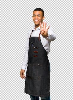 Молодой афро-американский парикмахер человек счастлив и считать четыре с пальцами