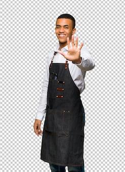 Молодой афро-американский парикмахер человек, считая пять с пальцами
