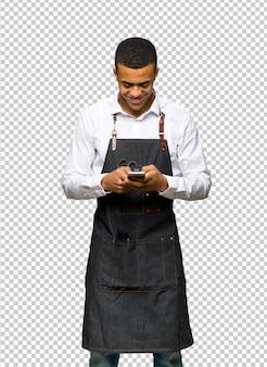 携帯電話でメッセージを送信する若いアフロアメリカンの理髪師男