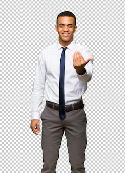 Молодой афро американский бизнесмен приглашая прийти с рукой. рад, что ты пришел