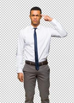 頭に指を置く狂気のジェスチャーを作る若いアフロアメリカンビジネスマン
