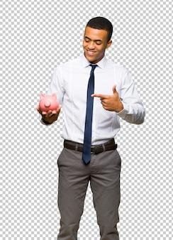 Молодой афро-американский бизнесмен держит копилку