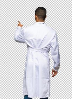 Молодой афро-американский мужчина доктор, указывая назад с указательным пальцем