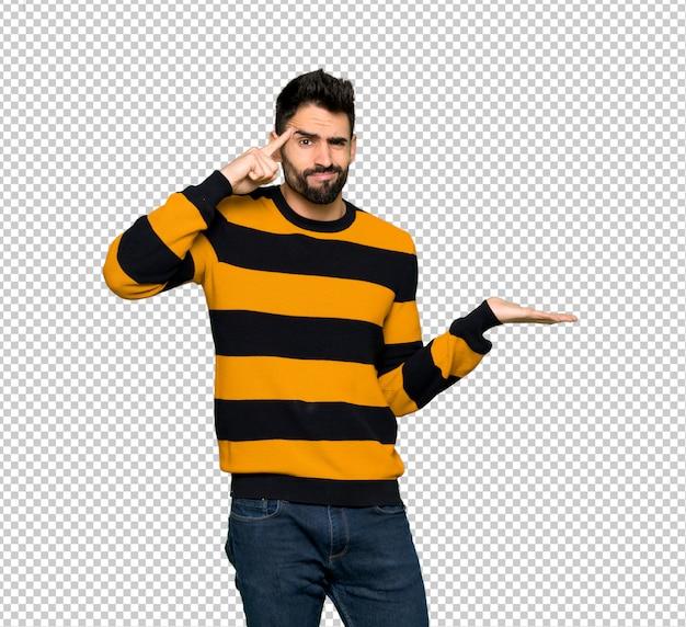 頭に指を置く狂気のジェスチャーを作る縞模様のセーターを持つハンサムな男