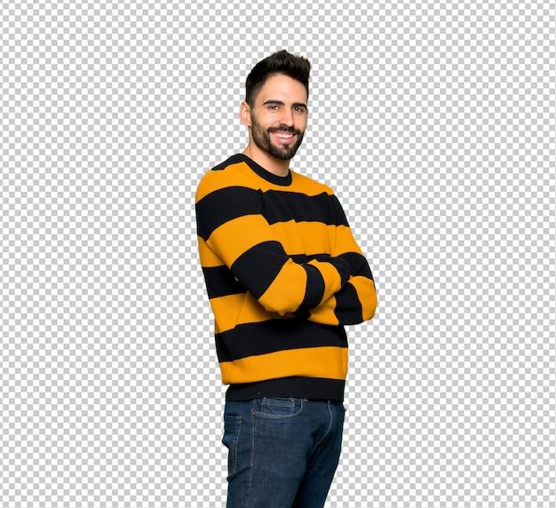 腕を組んで、楽しみにしてストライプのセーターを持つハンサムな男