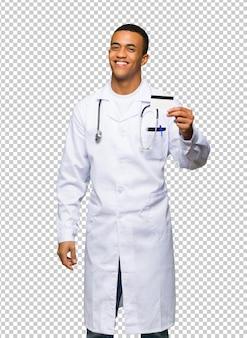 Молодой афро-американский мужчина доктор держит кредитную карту