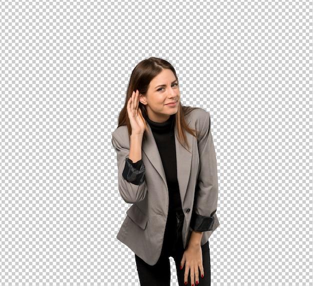 ビジネスの女性が耳に手を置くことによって何かを聞いて