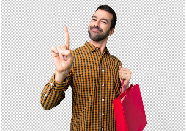 Человек с сумками, показывая и поднимая палец в знак лучших