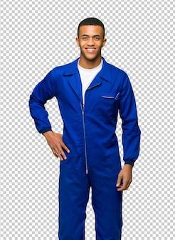 Молодой афро американский рабочий человек позирует с руки на бедра и улыбается