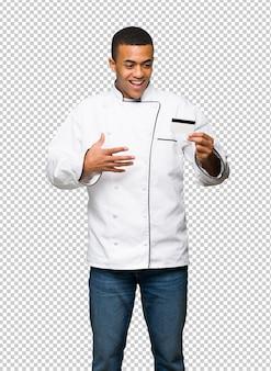 Молодой афро американский шеф-повар мужчина держит кредитную карту и удивлен