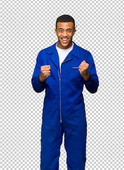 Молодой афро-американский рабочий человек празднует победу в положении победителя