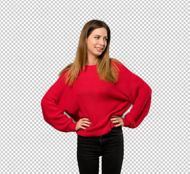 赤いセーターの腰に手でポーズと笑顔を持つ若い女