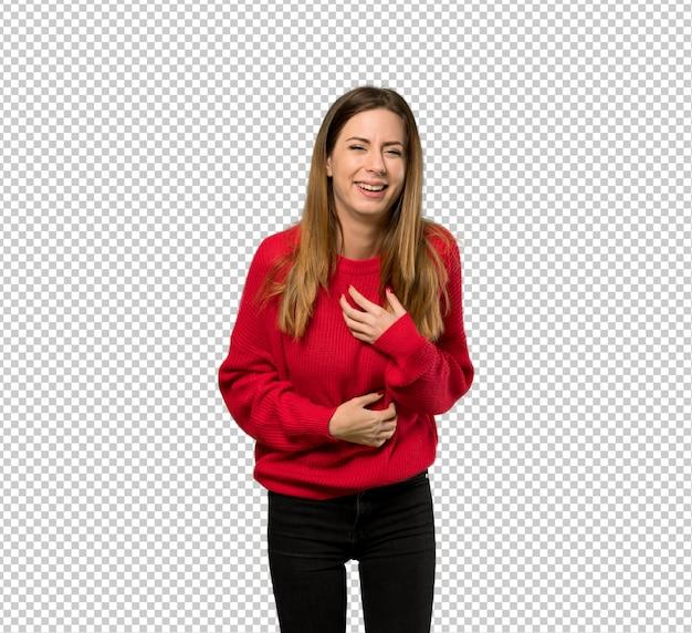 たくさん笑っている赤いセーターを持つ若い女