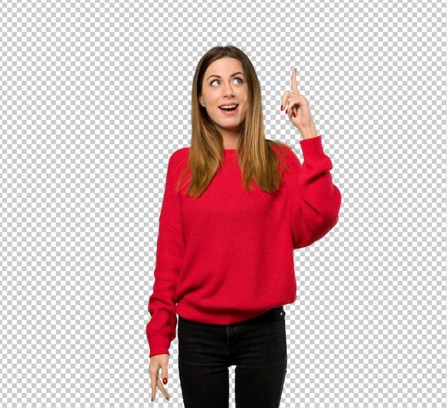指を持ち上げながら解決策を実現するつもりの赤いセーターを持つ若い女