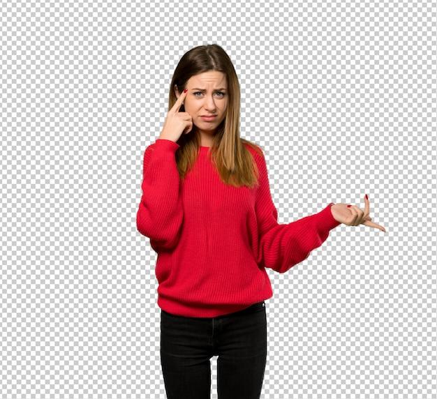 頭に指を置く狂気のジェスチャーを作る赤いセーターを持つ若い女