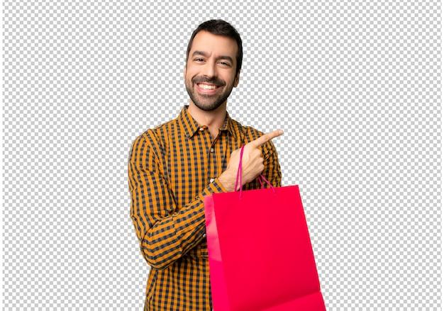 横位置で側に指を指している買い物袋を持つ男