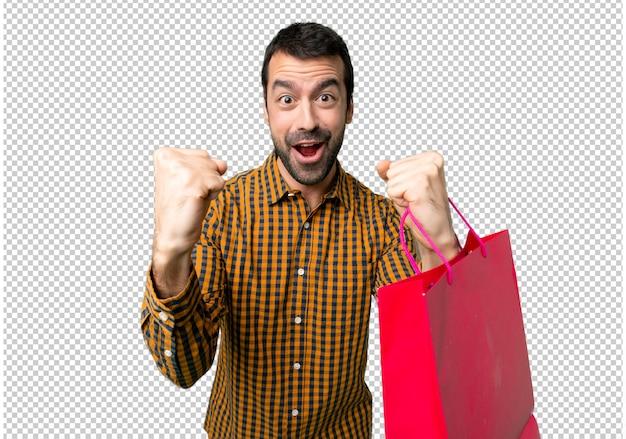 勝者の位置で勝利を祝っている買い物袋を持つ男