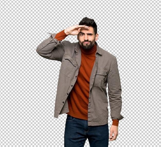Красивый мужчина с бородой, глядя далеко с рукой, чтобы посмотреть что-то