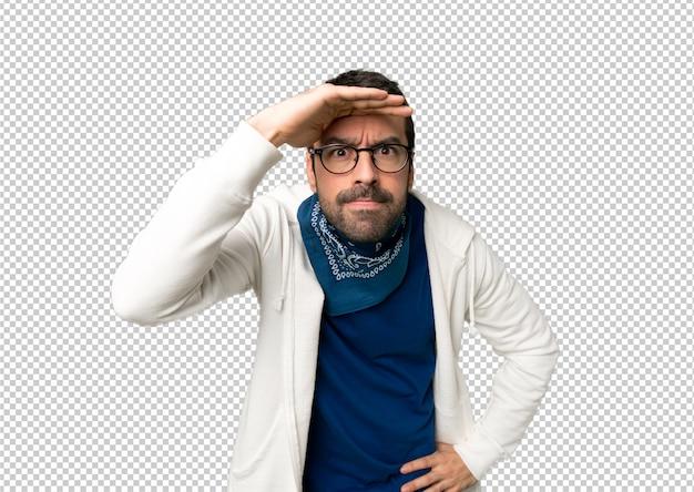 Красивый мужчина в очках смотрит далеко с рукой, чтобы посмотреть что-то