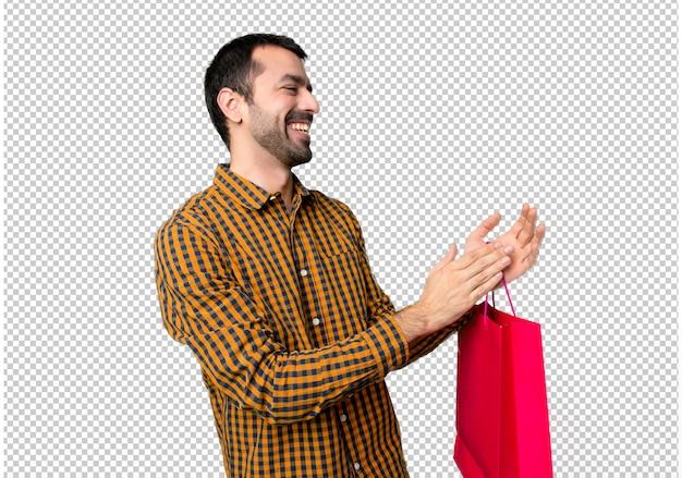 会議でのプレゼンテーションの後に拍手の買い物袋を持つ男