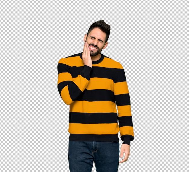 歯痛とストライプのセーターを持つハンサムな男