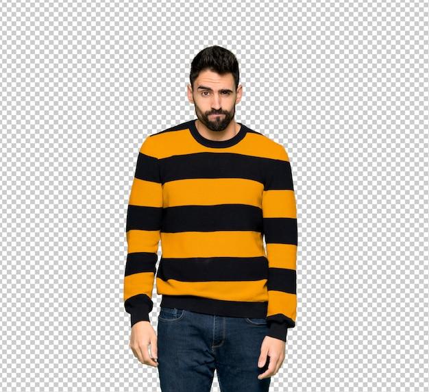 悲しいと落ち込んで式とストライプのセーターを持つハンサムな男