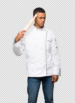 頭に指を置く狂気のジェスチャーを作る若いアフロアメリカンシェフ男