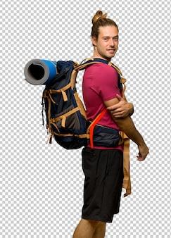 笑顔で肩越しに見ている山のバックパッカーを持つハイカー男