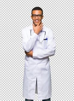 Молодой афро-американский мужчина доктор в очках и улыбается