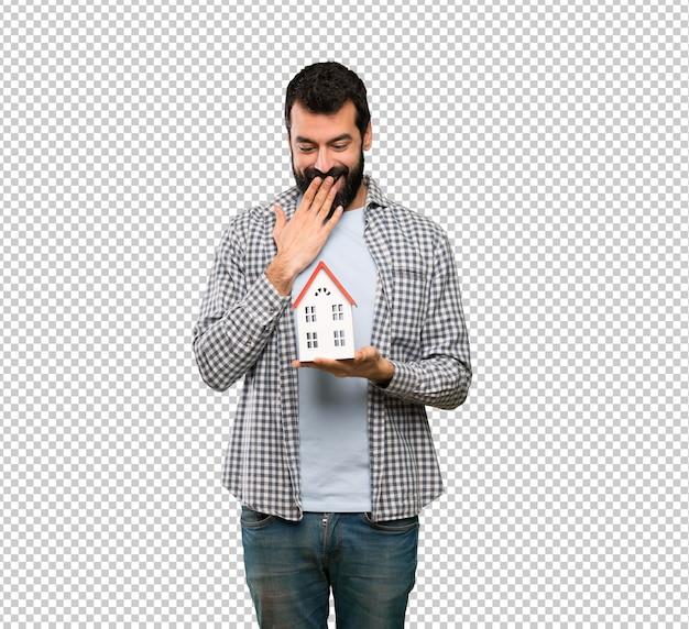 小さな家を保持しているひげを持つハンサムな男