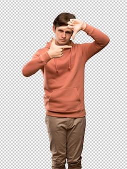 Подросток человек с фуфайка, сосредоточив внимание лица. обрамление символ