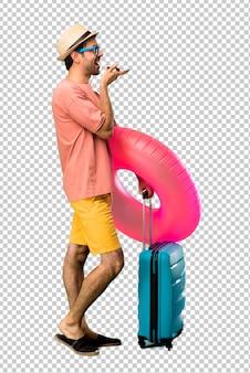 携帯電話に話している彼の夏休みに帽子とサングラスを持つ男