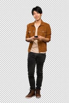 Полноразмерный снимок азиатского мужчины в коричневой куртке, отправляющего сообщение с мобильного телефона