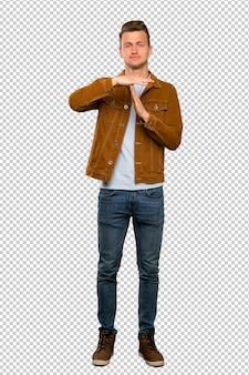 タイムアウトジェスチャーを作る金髪のハンサムな男のフルレングスショット