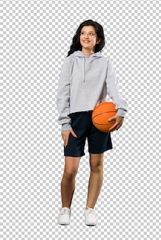 笑みを浮かべて見上げるバスケットボールをしている若い女性の全身ショット