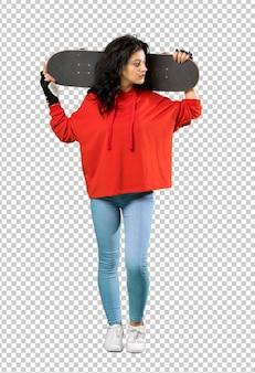 赤いスウェットシャツを持つ若いスケーター女性